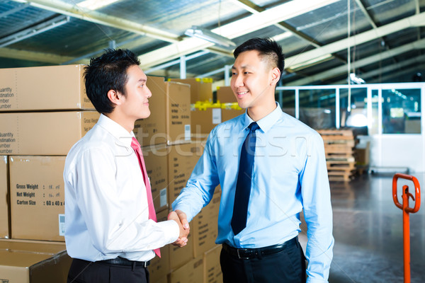 Businesspeople in warehouse have a deal Stock photo © Kzenon