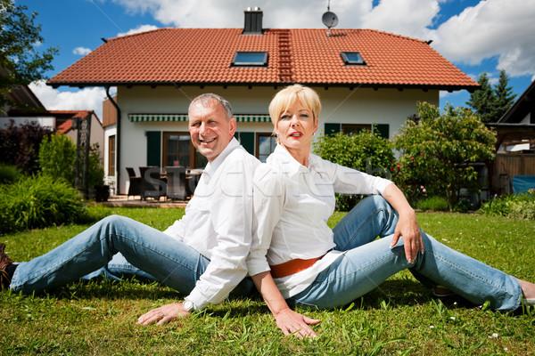 Senior couple sitting in front of their home Stock photo © Kzenon