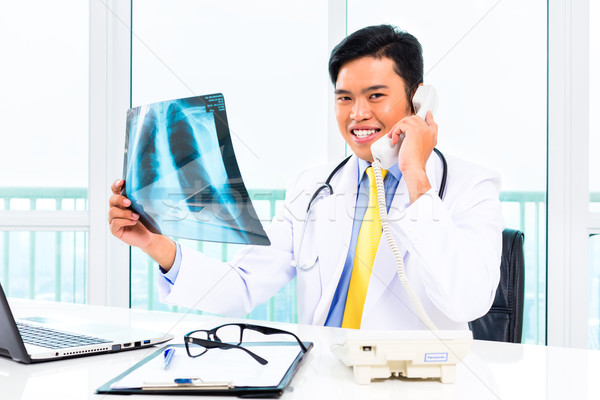 Asian doctor diagnosis radiograph in practise Stock photo © Kzenon