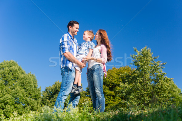 Family carrying kid, the parents standing on meadow Stock photo © Kzenon