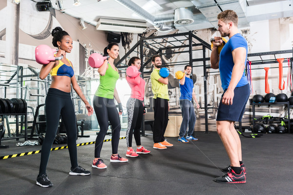 Men and women with coach at kettlebell functional training Stock photo © Kzenon