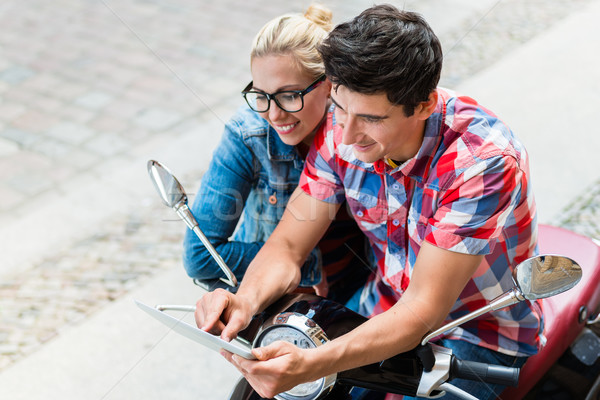 Couple on city trip planning their Vespa tour using tablet PC Stock photo © Kzenon