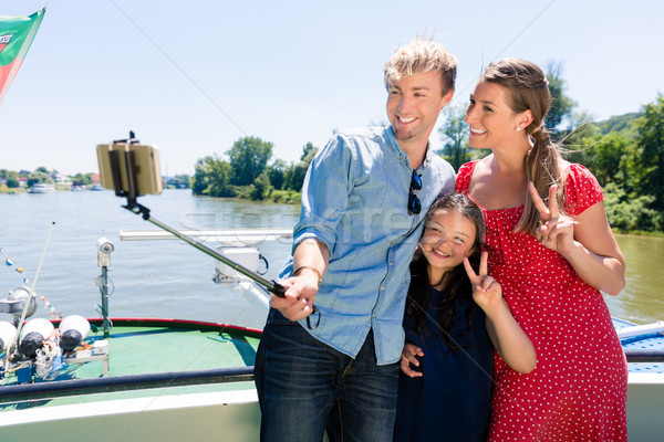 Family on river cruise with selfie stick in summer Stock photo © Kzenon