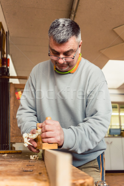 Experienced carpenter planing a board Stock photo © Kzenon
