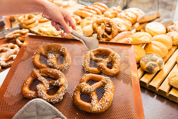 Sales lady in bakery shop selling pretzels and bread Stock photo © Kzenon