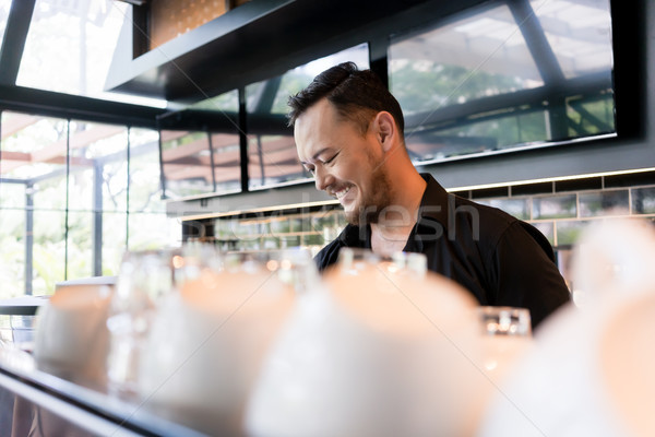 Happy young man working as barista behind the bar counter Stock photo © Kzenon
