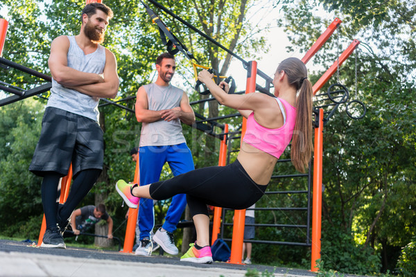 Athletic young woman doing bicep curls with a suspension trainer Stock photo © Kzenon