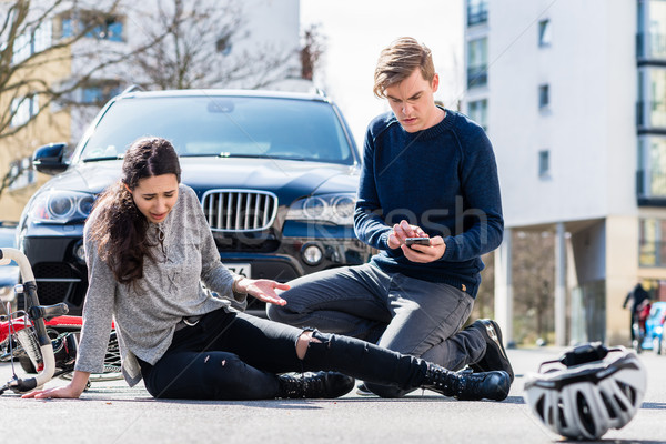 Worried young driver calling the ambulance after hitting female bicyclist Stock photo © Kzenon