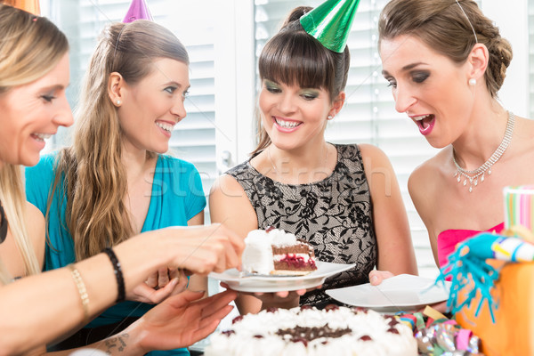 Four beautiful women and best friends smiling while sharing a birthday cake Stock photo © Kzenon