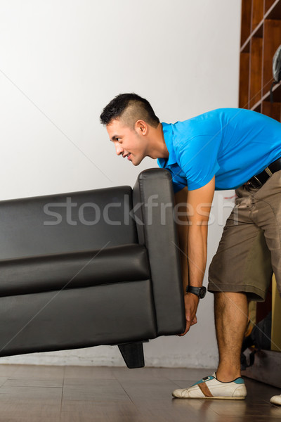 Young asian man lifting a couch Stock photo © Kzenon