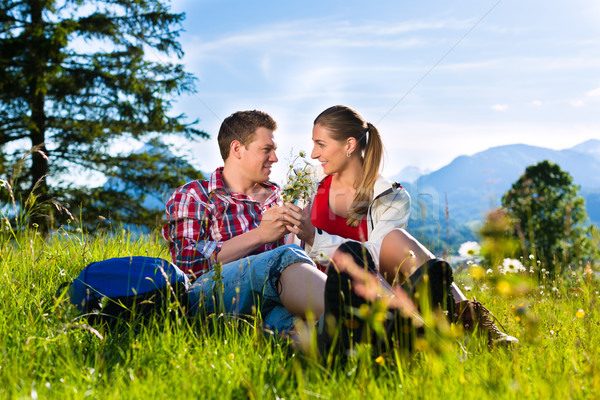 Couple is sitting in the meadow with mountain Stock photo © Kzenon