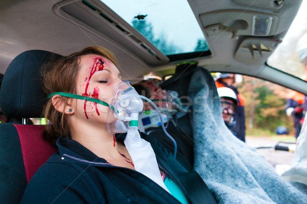 Car accident - Victim in crashed vehicle receiving first aid Stock photo © Kzenon