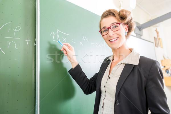 Teacher writing with chalk in front of school class on board Stock photo © Kzenon