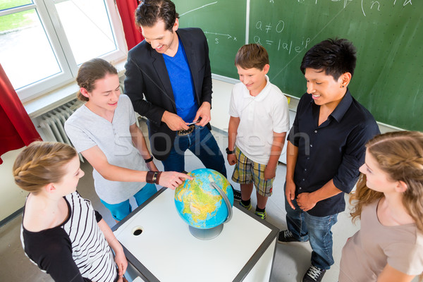 Stock photo: Teacher teaching students geography lessons in school