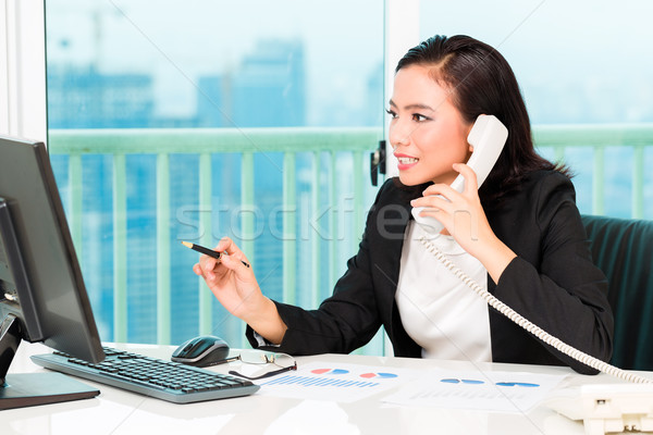 Asian Chinese businesswoman in office Stock photo © Kzenon