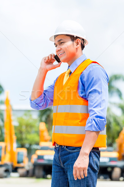 Asian supervisor telephoning on construction site Stock photo © Kzenon