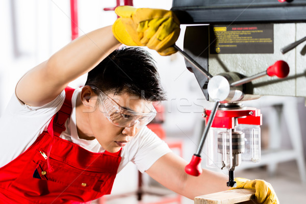 Chinese man working with drill in factory  Stock photo © Kzenon