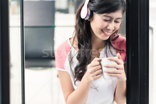 Indonéz nő élvezi zene otthon kávé Stock fotó © Kzenon