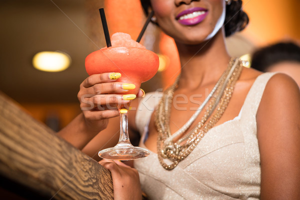 African Woman in bar drinking cocktail Stock photo © Kzenon