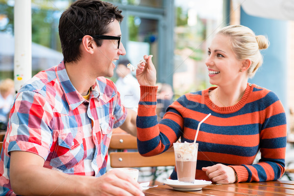 Couple having coffee in a street cafe Stock photo © Kzenon