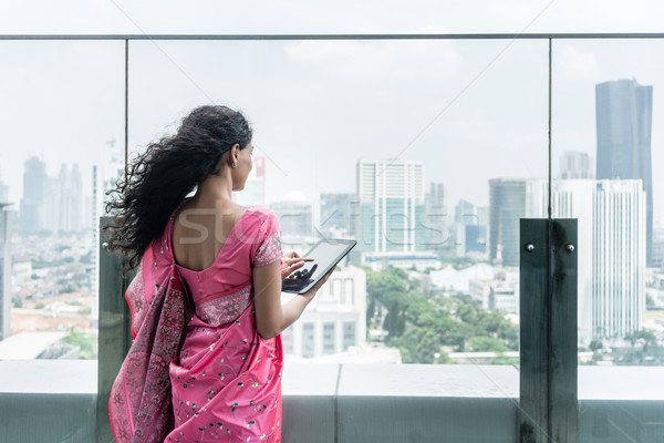Young Indian woman using a tablet Pc on a terrace in a windy day Stock photo © Kzenon