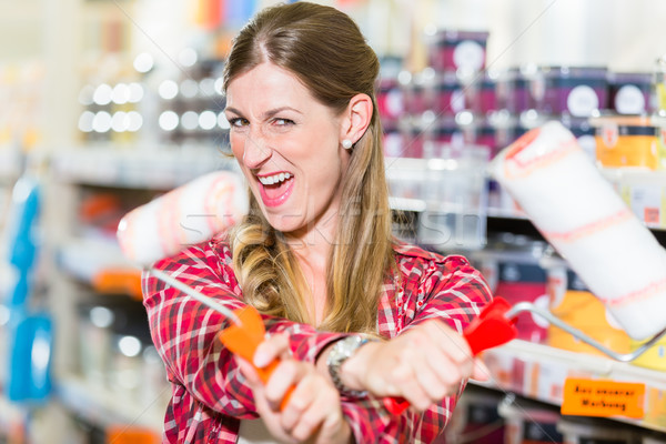 Woman in hardware store with paint rollers Stock photo © Kzenon
