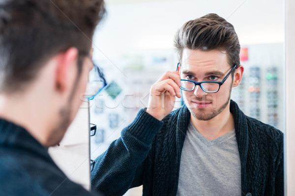 Man testing glasses in optician shop mirror Stock photo © Kzenon
