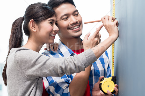 Young indonesian couple measuring walls in new apartment Stock photo © Kzenon