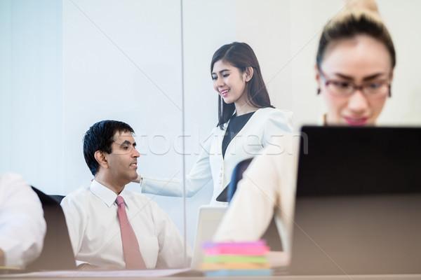 Office co-workers talking gossip behind back of businesswoman Stock photo © Kzenon