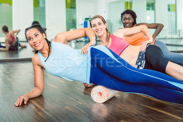Beautiful fit woman smiling during group workout class of foam r Stock photo © Kzenon
