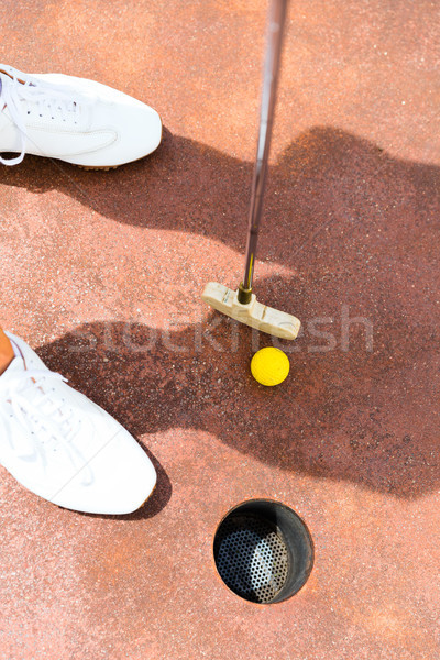 Woman playing miniature golf, holing in Stock photo © Kzenon