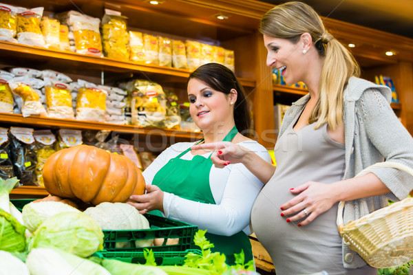 Woman buying pumpkin and vegetables in delicatessen Stock photo © Kzenon