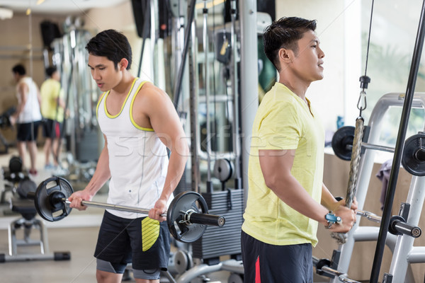 Young man exercising triceps pushdown at the rope cable machine  Stock photo © Kzenon