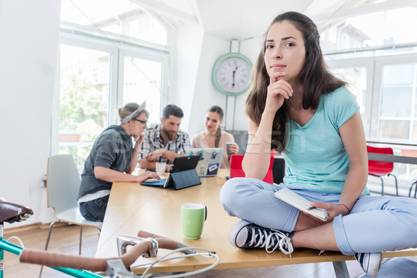 Beautiful young woman sitting on a desk during work Stock photo © Kzenon