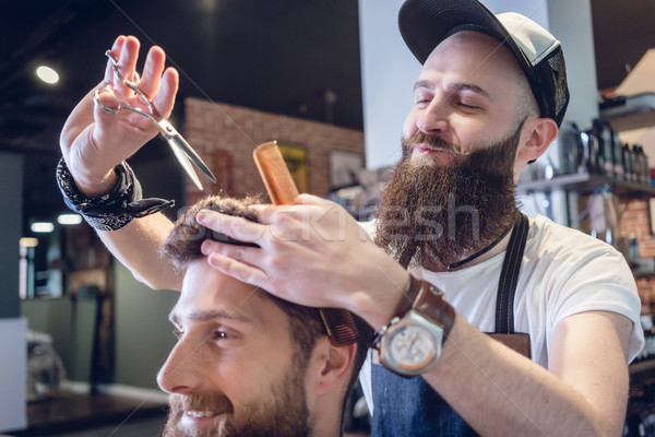 Dedicated hairstylist using scissors and comb while giving a cool haircut Stock photo © Kzenon