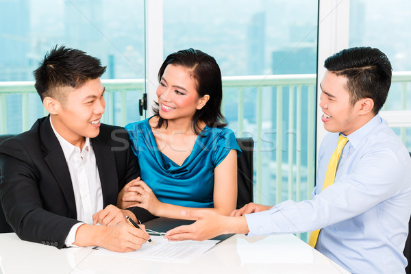 Asian banker selling insurance to couple Stock photo © Kzenon