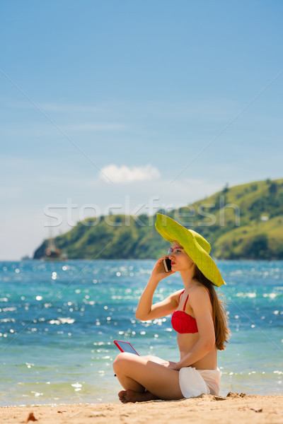 Fashionable young woman talking on mobile phone on the beach Stock photo © Kzenon
