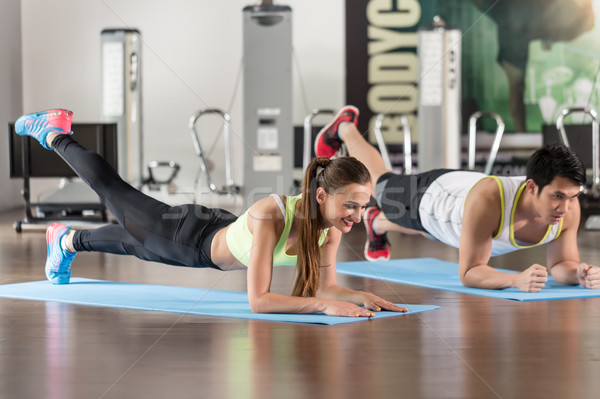 Determined woman exercising with her partner forearm plank at the gym Stock photo © Kzenon