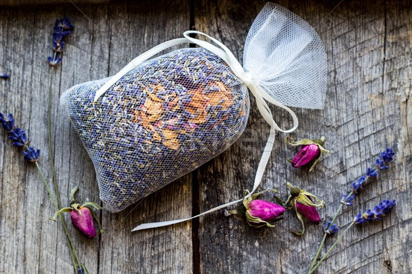 bag with wild roses petals and dried lavender flowers on wooden, vintage background - fragrance to t Stock photo © laciatek
