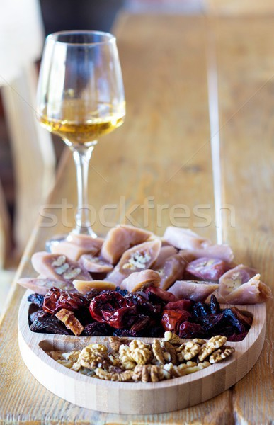 georgian snacks: walnuts, dried fruits and churchkhela and a glass of white wine  Stock photo © laciatek