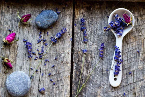 dried lavender and and flowers of wild rose, ceramic scoop and stones on wooden vintage background - Stock photo © laciatek