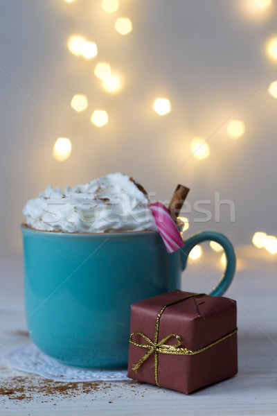 A cup of hot chocolate with whipped cream, a Christmas cane and a gift with bokeh in the background Stock photo © laciatek