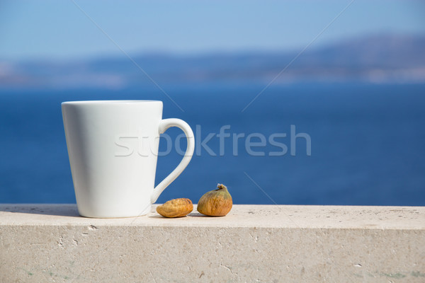 white cup with coffee and two figs on a background of blue sea and mountains Stock photo © laciatek