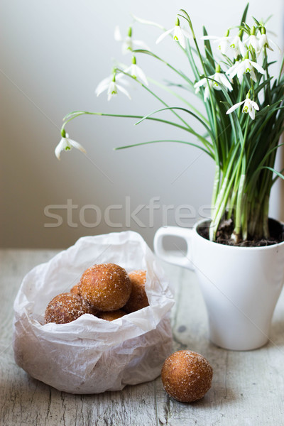 mini donuts in a paper bag and snowdrops flowers on a white, woode table Stock photo © laciatek
