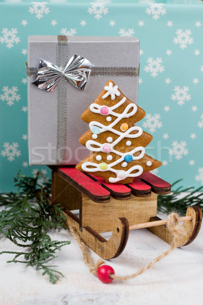 Gingerbread Christmas tree and gift on wooden sledge on a blue background Stock photo © laciatek