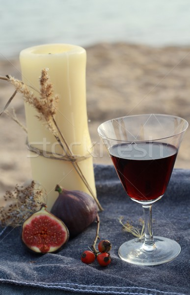 Candle and red wine on the beach  Stock photo © laciatek