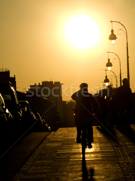 Bisikletçi gün batımı kaldırım köprü şehir kadın Stok fotoğraf © ldambies