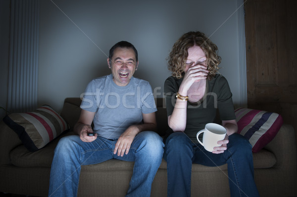 couple watching television laughing and embarrassed Stock photo © leeavison