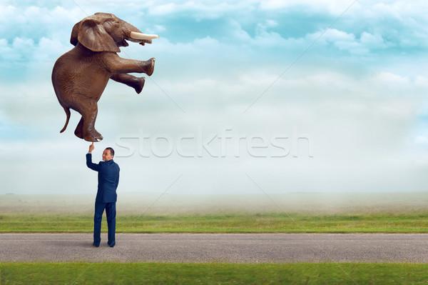 businessman holding an elephant with one finger  Stock photo © leeavison