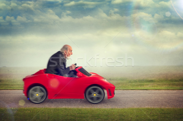 senior man driving a toy racing car Stock photo © leeavison